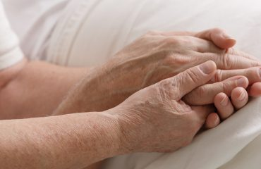 Elderly people holding hands in support on a hospital bed